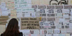Mulher observa mural de protesto contra o estupro de uma menina de 16 anos por 30 homens no Rio de Janeiro