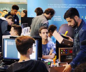 Três rapazes usando o computador e instrutor ensinando a montar um videogame.
