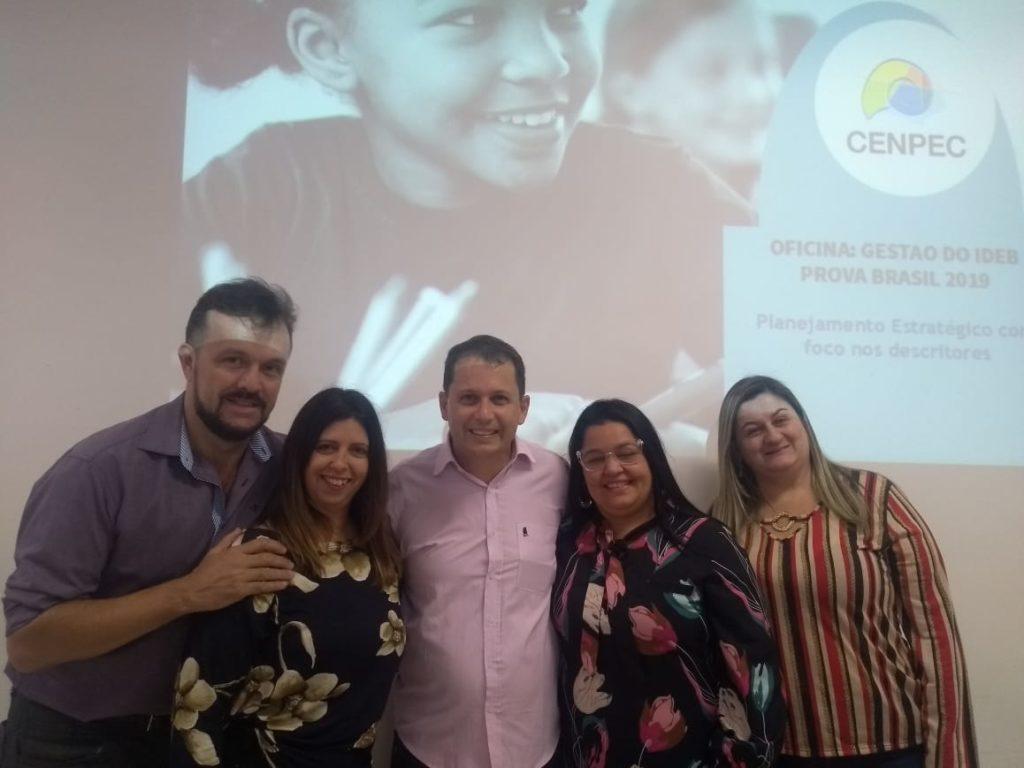 Na foto, cinco pessoas posam em frente à uma parece branca que está projetando o logo do CENPEC Educação.