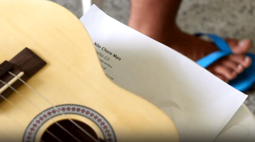 """Cena do documentário Meninos de palavra. Na imagem, vemos um violão sobre uma folha de papel com a letra da canção """"Não chores mais"""", de Gilberto Gil, e parte do pé de um menino interno"""