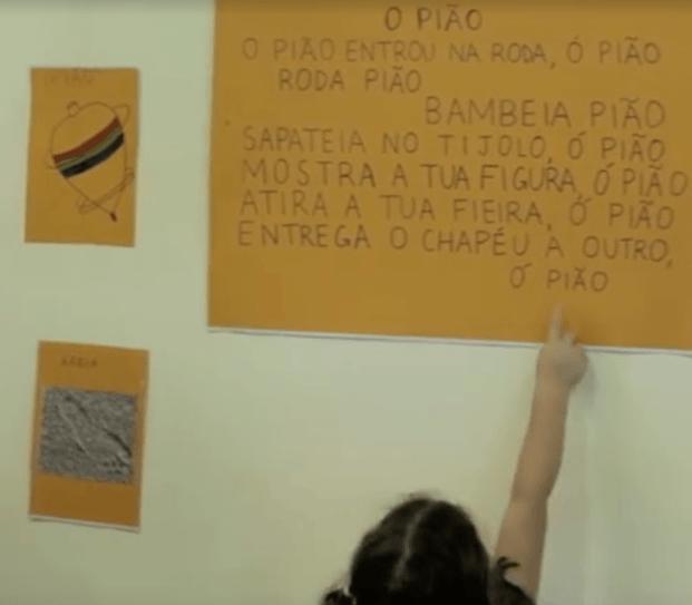 """Criança lendo cartaz com letra da cantiga de roda """"O pião"""""""