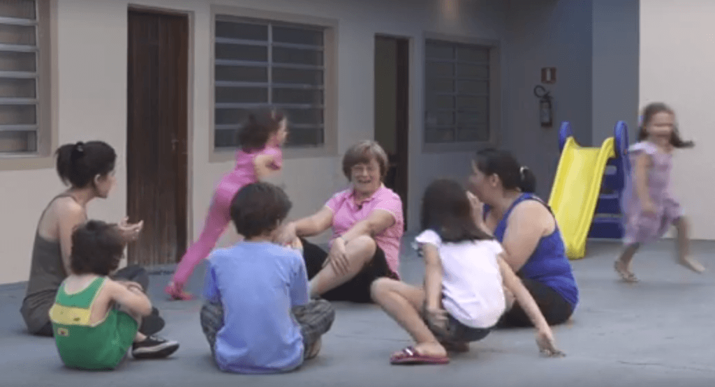 Crianças e educadores brincando de corre cotia