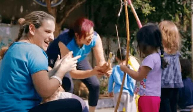 Educadores jogando capoeira com as crianças