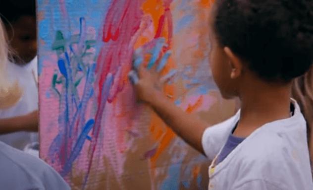 Crianças pintando mural coletivo
