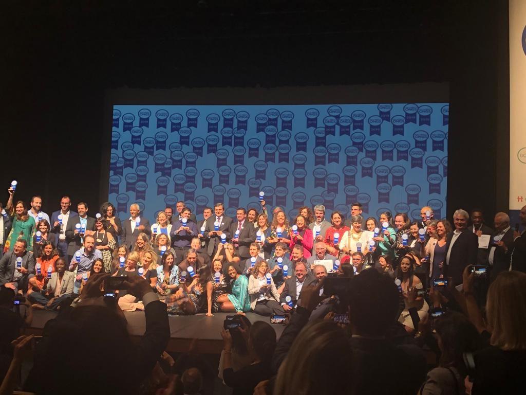 Representantes das 100 Melhores ONGs de 2019, na cerimônia realizada em São Paulo. Pessoas levantando os troféus 100 Melhores ONGs.