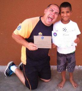 Gil Brasil e criança no Instituto Atleta Bom de Nota.