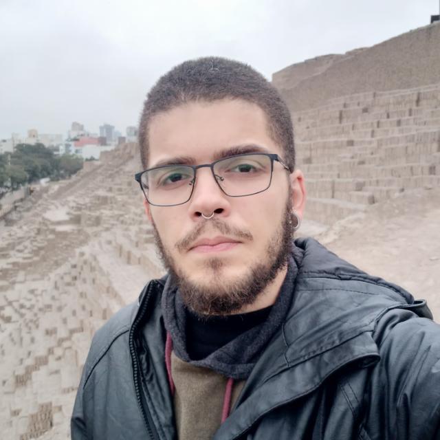 Professor Cássio Pacheco de Freitas está em pé em frente a um sítio arqueológico.