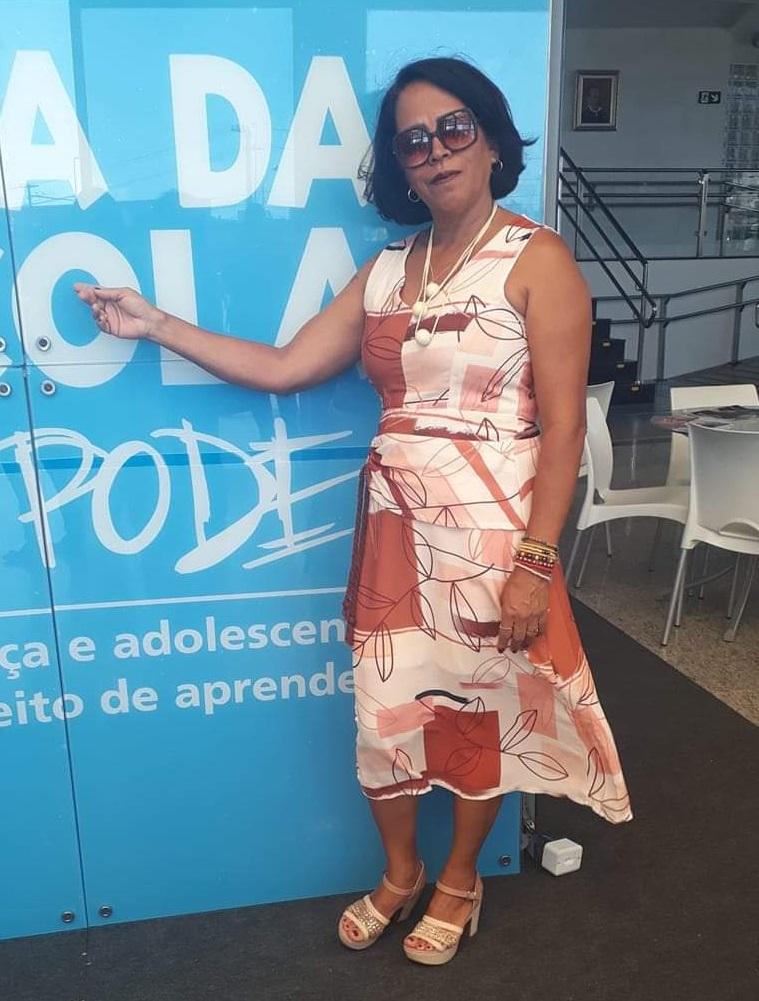 Gilva Cardoso, presidente do Conselho Municipal de Educação de Santo Estêvão (BA), está em pé em frente a um estande azul.