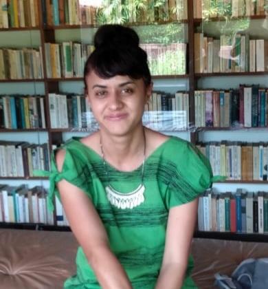 Fotografia de Claudiana Cabral, técnica do CENPEC Educação responsável pelo projeto. Há livros atrás dela.
