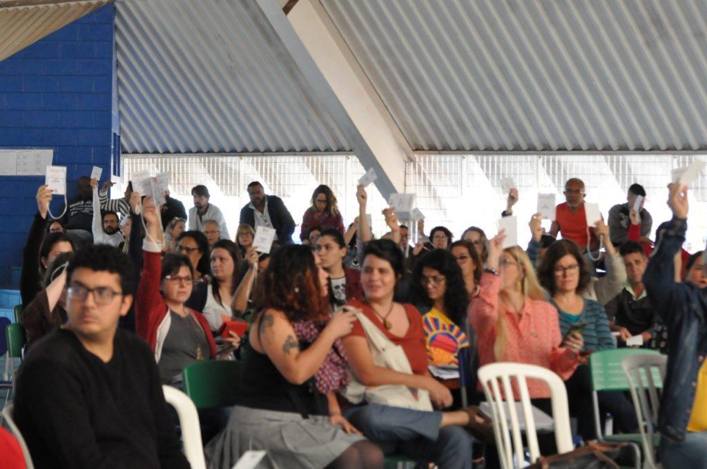 Imagem de um grupo de pessoas sentadas em cadeiras, sob um teto branco. Elas compareceram à primeira conferência de avaliação do Plano Municipal de Educação, em Campinas, São Paulo.