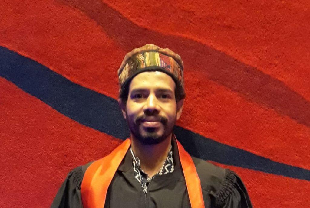 Imagem do professor Wesley Vieira em frente a um muro vermelho.