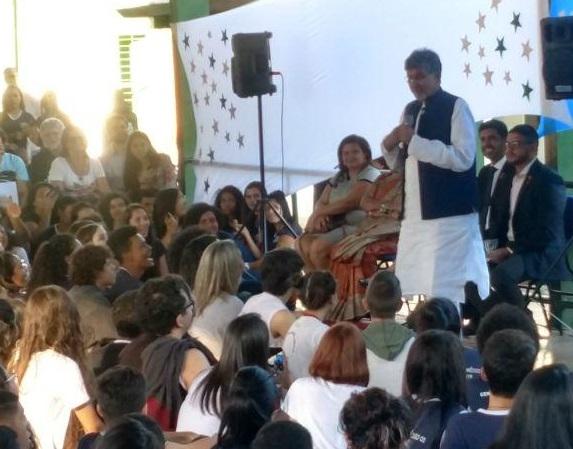 Fotografia da visita do indiano Kailash Satyarthi, vencedor do prêmio Nobel da Paz 2014, ao Centro de Ensino Médio Urso Branco (CEMUB). Ele discursa em pé, em frente a um toldo branco, e estudantes acompanham sentados no pátio da escola.