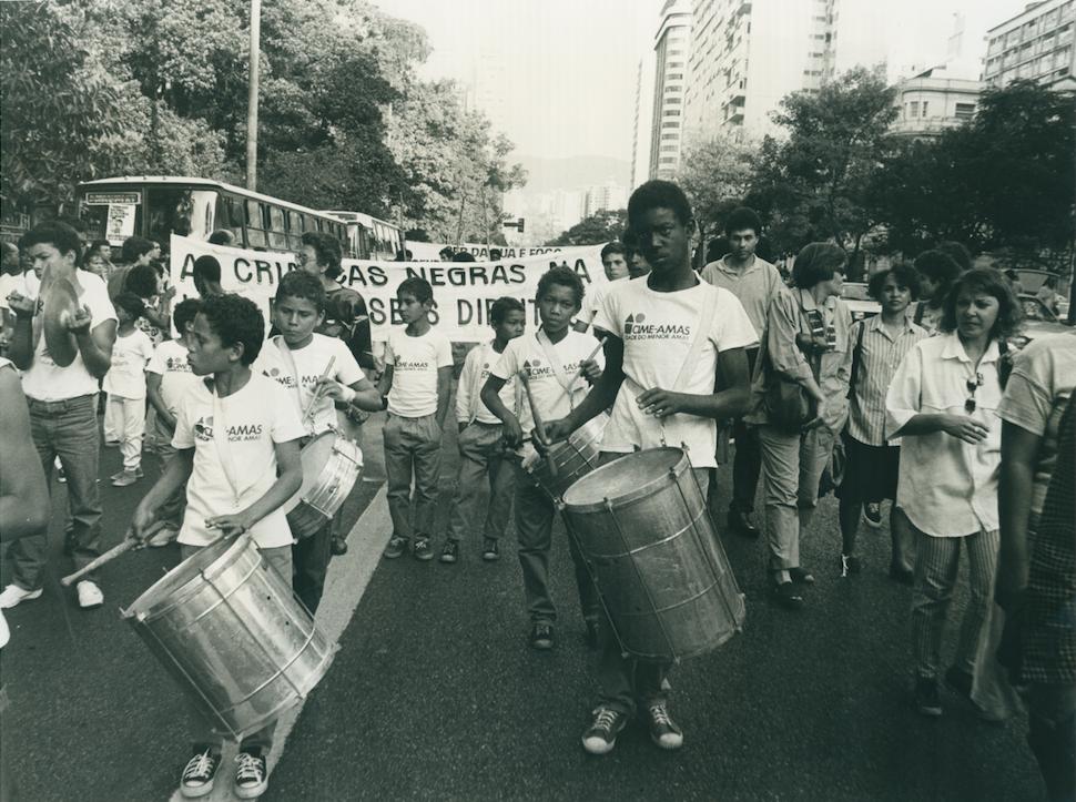 Imagem de manifestação de crianças e adolescentes pelos seus direitos. À frente das pessoas que compõem a manifestação, crianças e adolescentes tocam instrumentos de percussão.