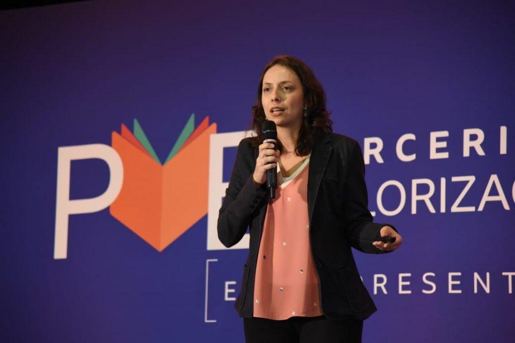 Fotografia de Carolina de Castro Nunes, analista de projetos sociais do Instituto Votorantim, durante uma apresentação do Programa Parceria pela Valorização da Educação (PVE)