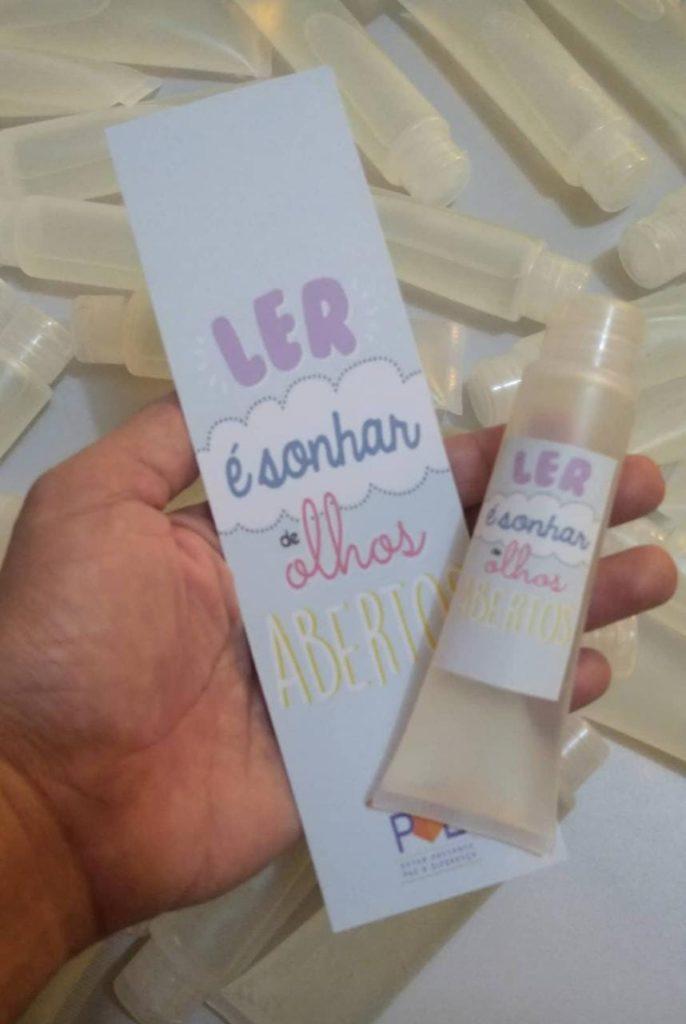 Imagem de marcador de livro e um frasco de álcool gel, entregues pelo projeto Delivery de livros na casa das pessoas.