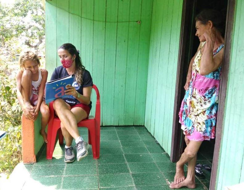 Imagem de uma cena de mediação de leitura, realizada por voluntários e voluntárias da ONG Vagalume na casa da família das crianças, em Cruzeiro do Sul (AC).