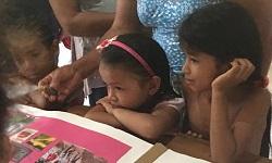 Imagem de crianças indígenas em frente a um livro.