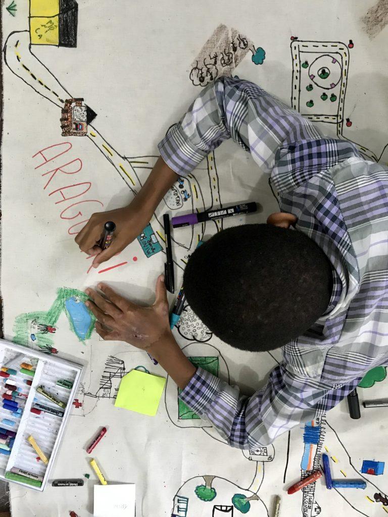 Estudante desenhando e escrevendo o mapa de seu território