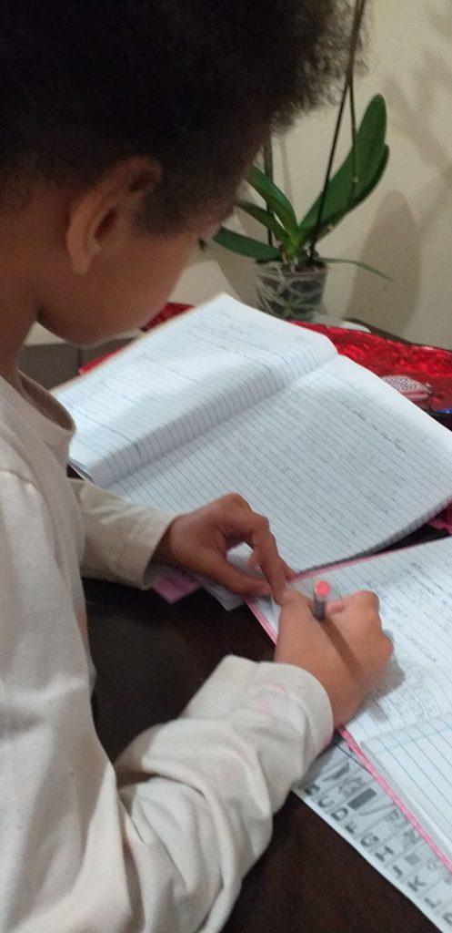 Menina escrevendo em caderno